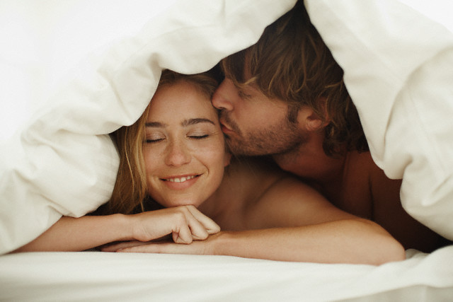 Young couple snuggling under a blanket --- Image by © Ole Graf/Corbis