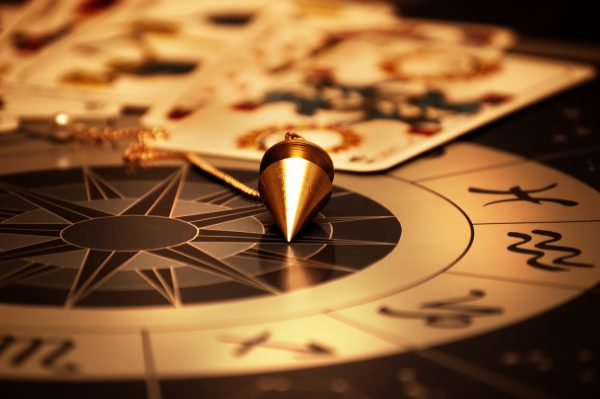 magic pendulum and cards of tarots on astrological background in special mystical lightning